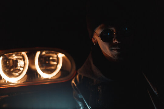 Stylish handsome man with sunglasses in fashionable clothes sits near headlights at night. Male silhouette in the dark