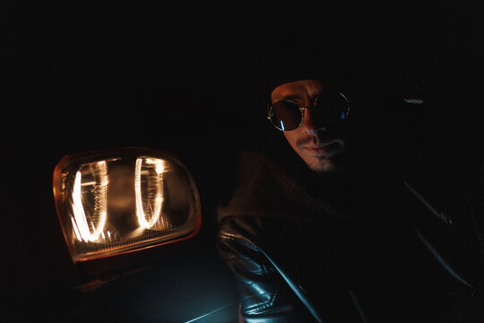 fashionable man with stylish sunglasses in black leather jacket sits near headlights at night