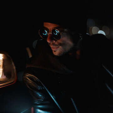 Fashion guy with stylish sunglasses with black leather jacket in the dark. Urban male casual style