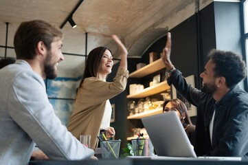 Two cheerful young business people giving high-five while their colleagues looking at them and...