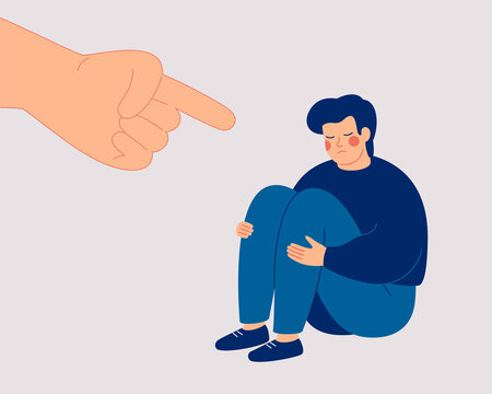 Sad boy suffers from psychological abuse from his peers. Depressed man sits on the floor and a big hand with an index finger is pointing at his. Public censure and victim-blaming. Bullying concept.