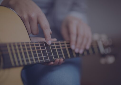 Close up of mid section of a person playing a guitar