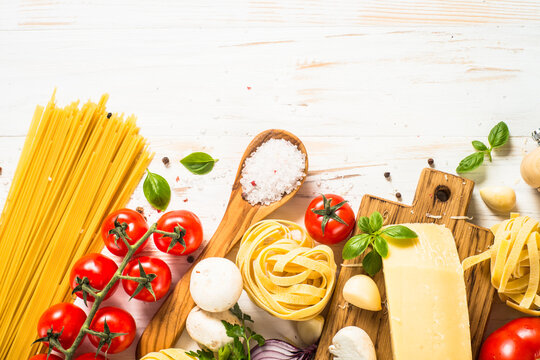 Italian food background on white wooden table. Pasta, fresh tomatoes, spices and basil. Top view with copy space.