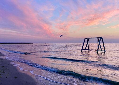 Swing near the sea at sunset