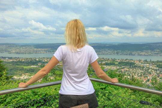 backside of woman looking Zurich city lake and skyline from top of Felsenegg cable car. Blonde tourist woman by lakefront in Deutch Switzerland of Canton of Zurich.