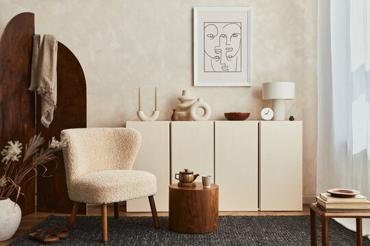 Creative composition of cozy living room interior design with mock up poster frame, fluffy armchair, folding screen, coffee table, commode and personal accessories. Modern style. Template.