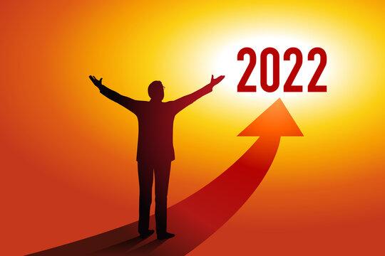 Carte de vœux 2022 montrant un homme d'affaires ouvrant les bras devant une flèche rouge en direction d'un horizon ensoleillé, symbole d'espoir et de réussite pour la nouvelle année.
