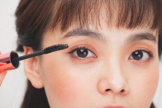 Pretty teen girl woman applying mascara isolated white background.