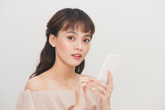 Portrait of asian attractive woman girl holding smartphone over white background
