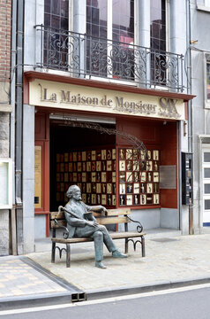 Dinant, Belgium 08-17-2014 Saxophone Museum and sculpture of Adolphe Sax on a bench