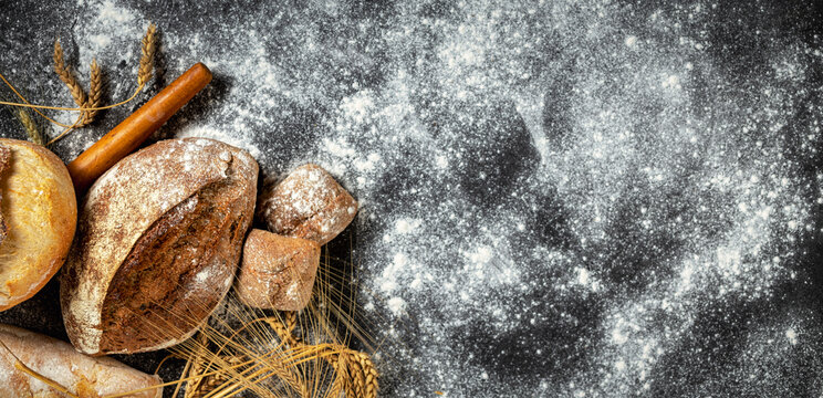 Bakery. Freshly baked crispy bread and buns with ears of wheat on a dark background with copy space top view