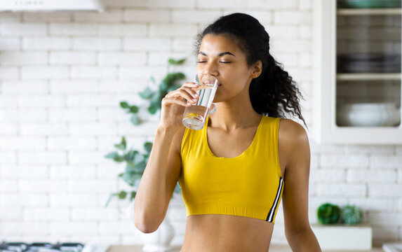 Young African American woman with beautiful body standing in the home kitchen, drinking fresh water. Healthy lifestyle concept