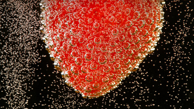Super slow motion of strawberry falling into champagne, macro shot.