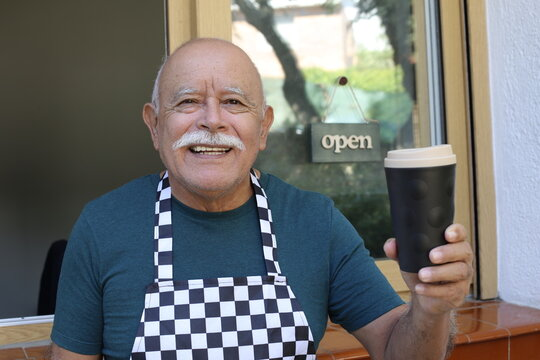 Welcoming senior waiter giving coffee away