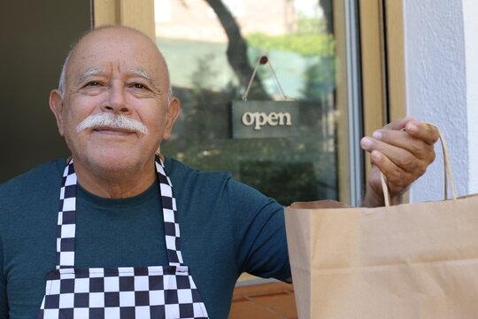 Senior service worker holding paper bag