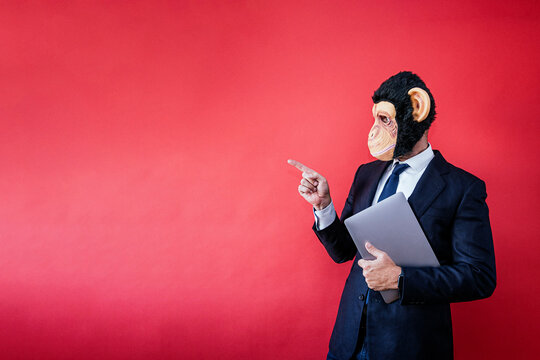 Businessman in monkey mask pointing to the side with a laptop under his arm