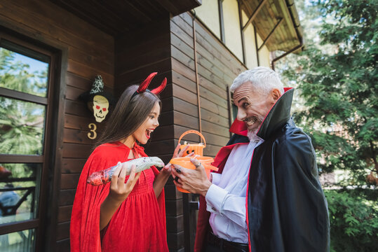 excited mature man in vampire halloween costume giving bucket of sweets to amazed daughter