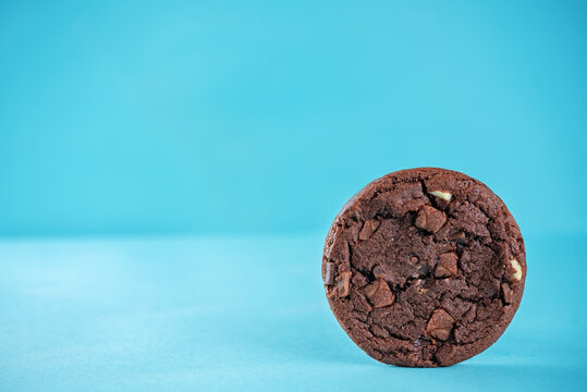 Chocolate cookies with dark and white chocoltae slices on a blue background