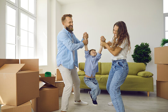 Happy family having fun in new home on moving day. Cheerful joyful excited young couple with child playing in living room with sofa and cardboard boxes. Real estate, mortgage, buying house concept