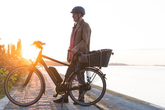man standing in front of electric bicycle