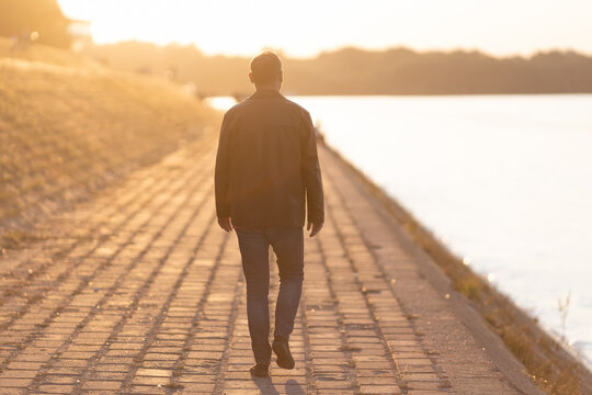 man walking away into sunset