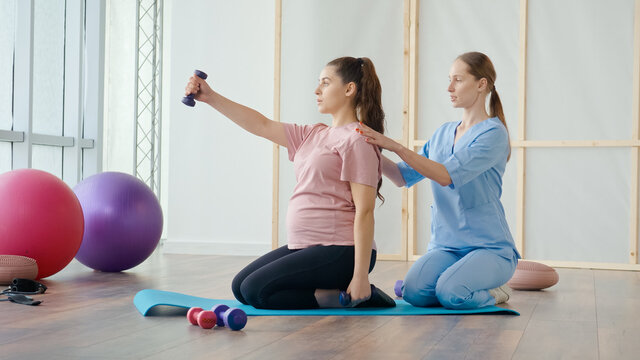 A Health Worker at a Medical Center Helps a Pregnant Woman to Do Exercises on a Ball with Dumbbells in Her Hands. The Expectant Mother Takes Care of her Health, Prepares for Childbirth.