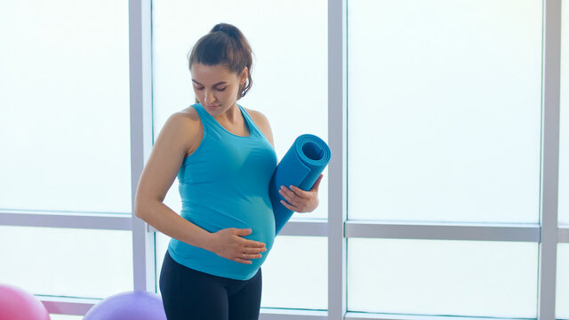 Close-up of a Pregnant Woman's Belly with a Sports Mat.