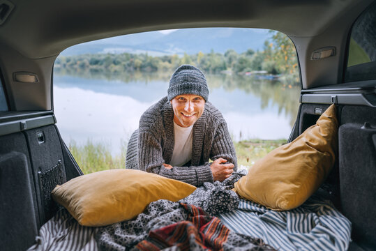 Sincerely smiling middle-aged man dressed in warm knitted clothes and jeans portrait in the cozy car trunk and with beautiful mountain lake view. Warm early autumn auto traveling concept image.