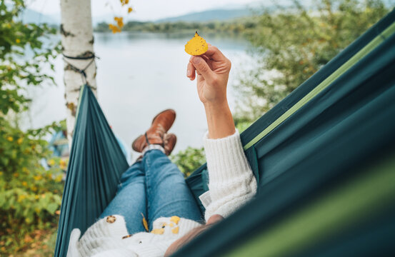 Young woman holding in fingers and examining small yellow birch tree leaf as she swinging in hammock on the mountain lake bank. Out-of-town Outdoor Recreation in Nature concept image.