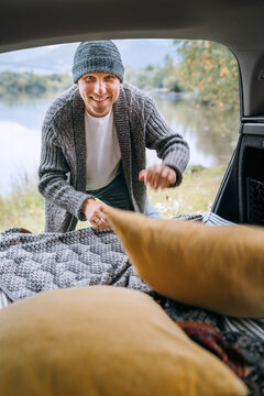Sincerely smiling middle-aged man dressed in warm knitted clothes preparing a sleeping place in cozy car trunk on beautiful mountain lake bank. Warm early autumn auto camper traveling concept image.
