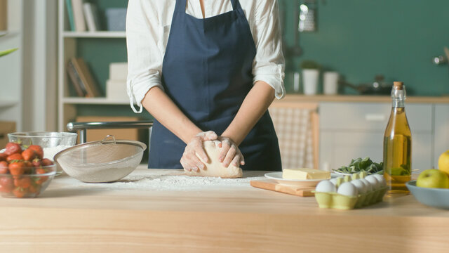 Professional Chef Kneads Dough for Baking on a Wooden Kitchen Table. The Process of Making a Beautiful Dough. Homemade Cakes for a Pastry Coffee Shop. Close-up.