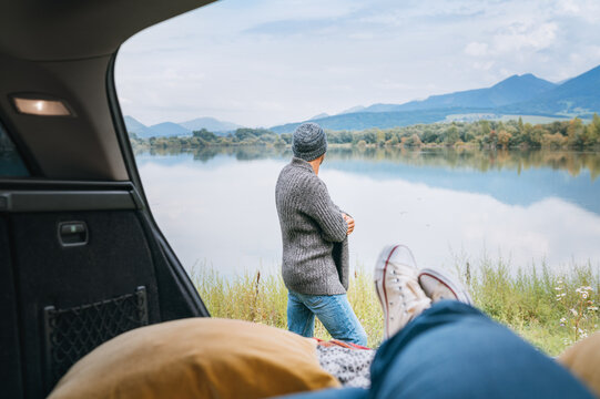 Car trunk view with woman legs in white sneakers on the man dressed warm knitted clothes and jeans enjoying the mountain lake view. Cozy early autumn couple auto traveling concept image.