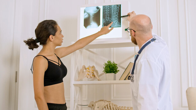 The Doctor Shows the Young Woman her X-ray, Evaluating the Patient's Condition in Order to Suggest Appropriate Treatment.