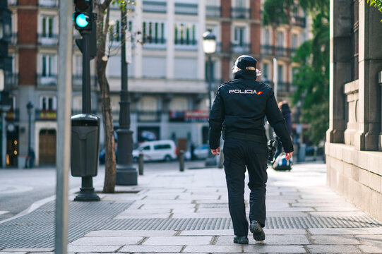 Policewoman member of the Spanish security forces and bodies walking down a city street