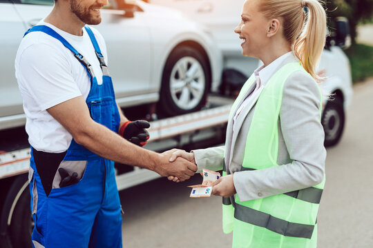 Elegant middle age business woman paying for towing service. Roadside assistance concept.