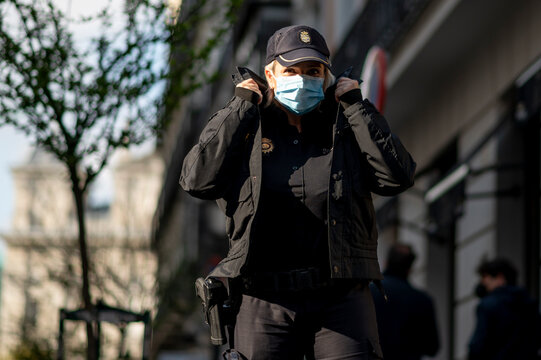 Police woman member of the security forces of Spain posing with a mask - New normal concept