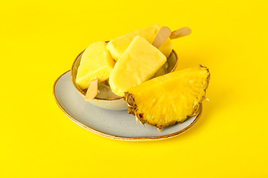 Plate with tasty pineapple popsicles on color background