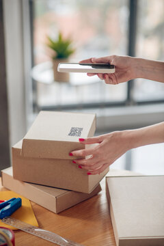 Female with red nails holding her smartphone over a cardboard box
