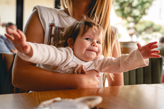 Small caucasian baby with arms wide spread while sitting by the table mother holding her infant daughter at restaurant real people