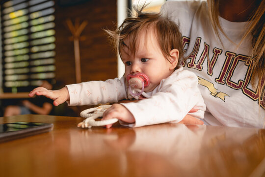 Small caucasian baby in hands of her mother trying to reach mobile phone on the table at cafe or restaurant in bright day real people childhood concept side view