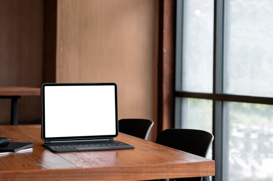 Blank screen tablet with magic keyboard and gadget on wooden table in meeting room.