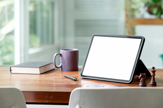 Mockup blank screen tablet on wooden table in living room.
