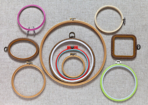 Top view of various types of wooden and plastic folding hoops for hand embroidery with cross-stitch and satin ribbons on special natural canvas. Set of accessories for embroidery. Flat lay, close-up