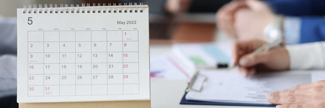 Loose leaf paper calendar standing on table against background of business people closeup