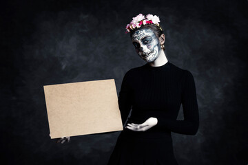 Obraz Woman with face painted as a Catrina and flowers in her hair on dark background pointing at poster. Day of the Dead - fototapety do salonu