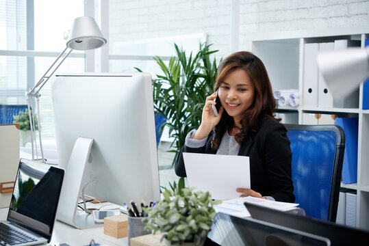 Pretty smiling female entrepreneur talking on phone with colleague from another department when looking at sales report in her hands