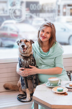 Portrait of smiling pregnant Caucasian women with her dog in cafe. Pregnant lifestyle.