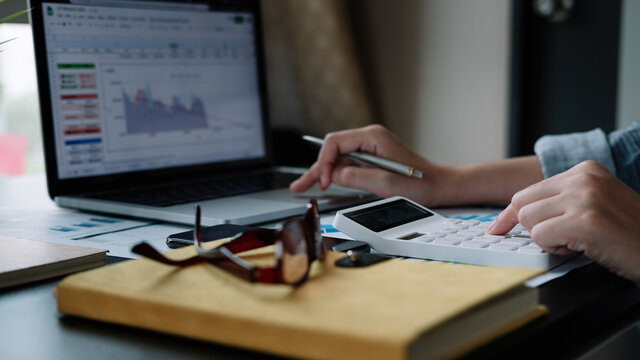 Close up hand woman doing finance and calculate with calculator on desk about cost , work from home concept