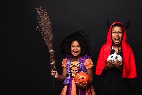 excited african american kids in halloween costumes holding carved pumpkins isolated on black
