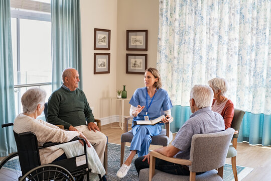 Nurse talking to senior people during group therapy